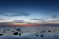 Sunset over the Baltic sea. Landscape with rocks in water royalty free stock images