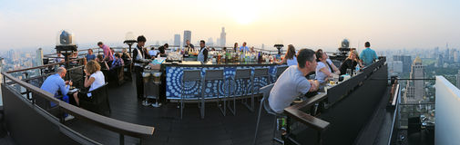 Sunset over Bangkok viewed from a roof top bar with many tourists enjoying the scene Stock Photo
