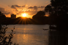 Sunset over Bardag Lake. The sun drops behind the trees as the waterfowl find shelter for the night Stock Images