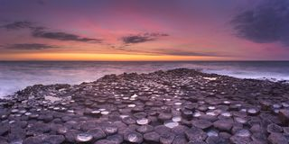 The Giant`s Causeway in Northern Ireland at sunset. Sunset over the basalt rock formations of Giant`s Causeway on the north coast of Northern Ireland stock image