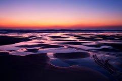 Sunset over beach. Orange sunset over Chapel Porth beach in Cornwall Stock Photos