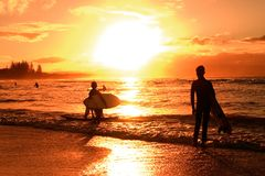 Sunset over beach. Kids with surfboards silhouetted against sunset over beach Stock Photos