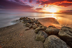 Sunset over a beach with large rocks Royalty Free Stock Photo