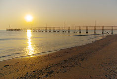 Sunset over beach and pier. Scenic view of golden sunset over sea, sandy beach and pier Stock Photography