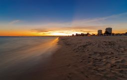 Sunset over the beach Praia Alvor. Sunset on the beach praia dos tres irmaos near Portimao, in the background the city of Lagos Royalty Free Stock Image