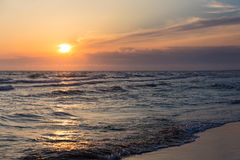 Sunset over beach sea tide sand coast seashore Stock Photography