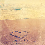 Sunset over beach on shore with love heart in the sand Stock Image