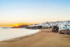 Cliffs, sandy beach and white architecture of Albufeira, Algarve. Sunset over beautiful cliffs between sandy beach and white architecture of Albufeira, Algarve Royalty Free Stock Photos