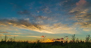 Sunset over big field. Cloudy sky timelapse stock video footage