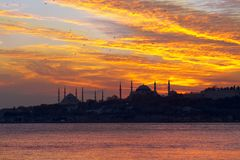 Sunset over Blue Mosque and Hagia Sophia. Setting sun fired up the sky and Bosphorus waters in Istanbul Stock Image
