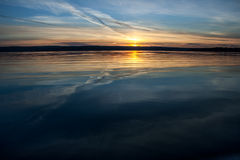 Sunset over blue water. Sunset over deep blue water in the quiet summer evening Stock Images
