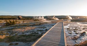 Sunset over boardwalk at the Old Faithful geyser basin in Yellowstone National Park in Wyoming USA stock images
