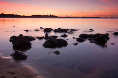 Sunset over boats with rocks in foreground Stock Images