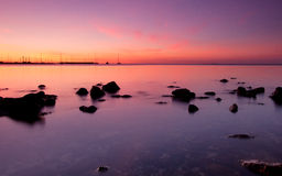 Sunset over boats with rocks in foreground Royalty Free Stock Image