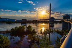 Sunset over Bob Kerrey Pedestrian bridge and swollen Missouri River at Omaha Riverfront. Sunset over Bob Kerrey pedestrian bridge and swollen Missouri River at royalty free stock image
