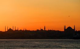 Sunset over the Bosporus. The plane takes off over the silhouettes of the Blue Mosque. royalty free stock image