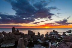 Sunset over breakwater Stock Photo