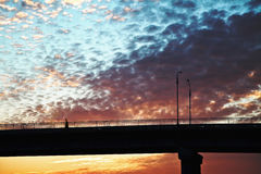 Sunset over the bridge, the bridge in the sun, beautiful yellow-orange clouds over the bridge Stock Photography