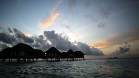 Sunset over bungalows, Maldives stock video