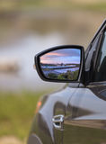 Sunset over a California highway in the rear view mirror of a ca. R in summer on a road trip Stock Photos