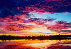 Sunset over calm lake. Colorful sunset reflected in calm lake water with glowing clouds overhead stock photos