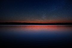 Sunset over Calm Lake with Real Stars in Dark Sky. A beautiful sunset over a calm lake with a black forest on the horizon and real stars in the sky Stock Photos