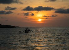 Sunset over calm ocean with balinese boat royalty free stock image