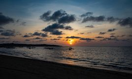 Sunset over calm ocean with balinese boat stock photos