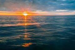 Sunset over calm ocean water. Minimalist glowing sunset over calm ocean water Royalty Free Stock Photos