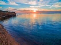 Sunset over calm ocean water. Sunset over calm ocean water near rugged coastal cliffs Royalty Free Stock Photos