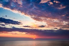 Sunset over calm sea in summer with sun beam. Europe Stock Images
