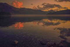 Sunset over the calm waters of a lake in patagonia stock images