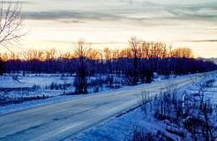 Sunset over the Canadian Rockes. Icy country road leading to the Canadian Rockies through rural Alberta Stock Photography