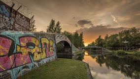 Sunset over a canal, with a graffiti covered bridge in the foreground Royalty Free Stock Photo