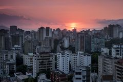 Sunset over Caracas City, Westside view, Venezuela. As the sun sets over Caracas city, the clouds get tainted in orange and contrast with the deep blue and stock photo