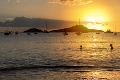 Sunset over Caribbean sea in Guadeloupe. View from Malendure beach towards Ilet Pigeon and Reserve Cousteau. Silhouettes of two unidentified persons swimming Stock Images