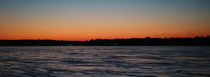 Sunset over Charlevoix lake Michigan. Frozen lake during winter Stock Images