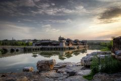 Sunset over a chinese style castle in a lake with a bridge and rocks in the foreground. Beautiful clouds at sunset over a chinese style castle in a lake with a stock image