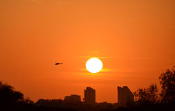 Sunset over the city. Beautiful sunset over the city with an helicopter passing through Royalty Free Stock Image