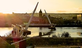 Sunset over the City. Of Londonderry, Northern Ireland. The Peace Bridge, symbol of peace and hope, over the river Foyle Stock Photos