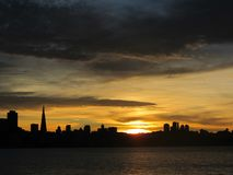 Sunset Over The City Of San Francisco Under Cloudy Skies. And calm water Royalty Free Stock Photography