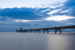 Sunset over Clevedon Pier, North Somerset, England, UK. Long exposure landscape image of sea and pier with the soft light at sunset, Clevedon, Somerset, England royalty free stock photos