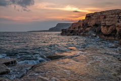 Sunset over cliffs and ocean Stock Images