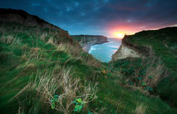 Sunset over cliffs in ocean Stock Image