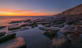 Sunset over cliffs in South Wales. Spectacular sunset reflecting on a tidal movement around large rocks, against a set of high cliffs Stock Photos