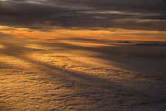 Sunset over Clouds with Mountain Tops from Plane. Sunset over Clouds with Mountain Tops cutting the Clouds - Airplane shot from Cockpit Royalty Free Stock Images