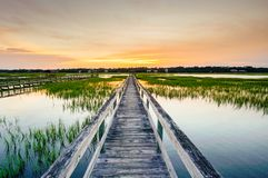 Sunset over coastal waters with a very long wooden boardwalk. Coastal waters with a very long wooden boardwalk pier in the center during a colorful summer sunset royalty free stock photo