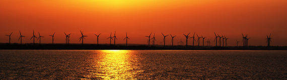 Sunset over coastal wind farm stock image