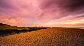 Sunset Over the Coastline. Pink, purple and gold sunset over the Chesil Beach Coastline on the South of England Royalty Free Stock Photos