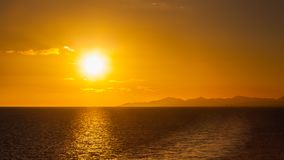 Sunset Over the Coastline of the Spanish Canary Island of Lanzarote. A yacht can be seen passing under the sun on the horizon Stock Photo